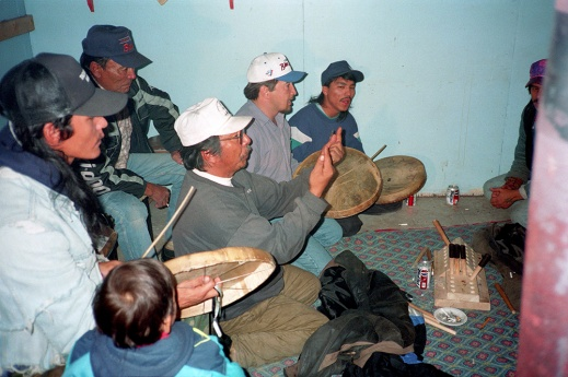 A colour photograph of six men and one small child. The men are playing Dene Handgame. Three of the men are hitting individual caribou-skin hand drums with wooden drumsticks and singing.