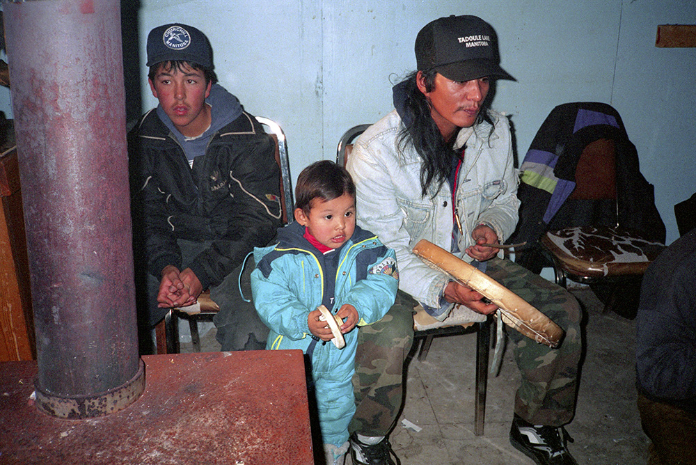 A colour photograph of a man, a teenage boy and a small child watching a Dene Handgame match. The man is hitting a caribou-skin hand drum with a wooden drumstick. The small child is mimicking the drumbeat with his own small hand drum.