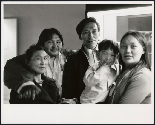A black-and-white photograph of four adults and a child smiling at the camera.