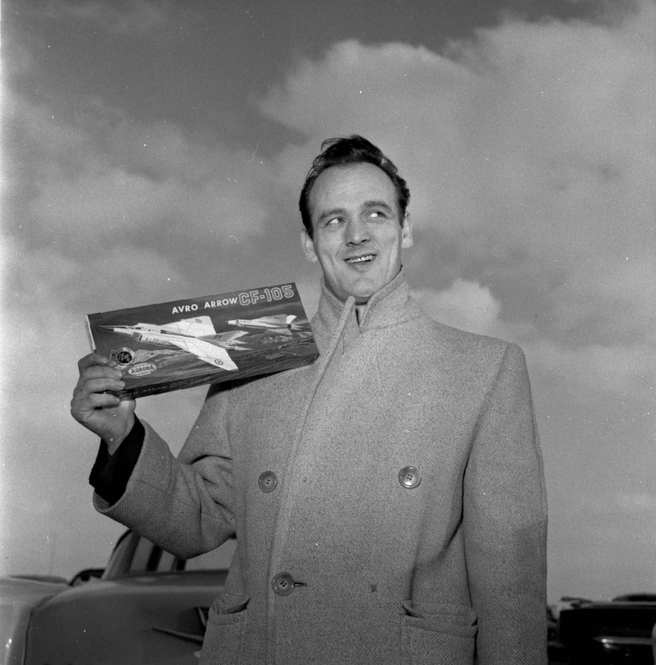 A black-and-white photograph of a man holding a model airplane kit.