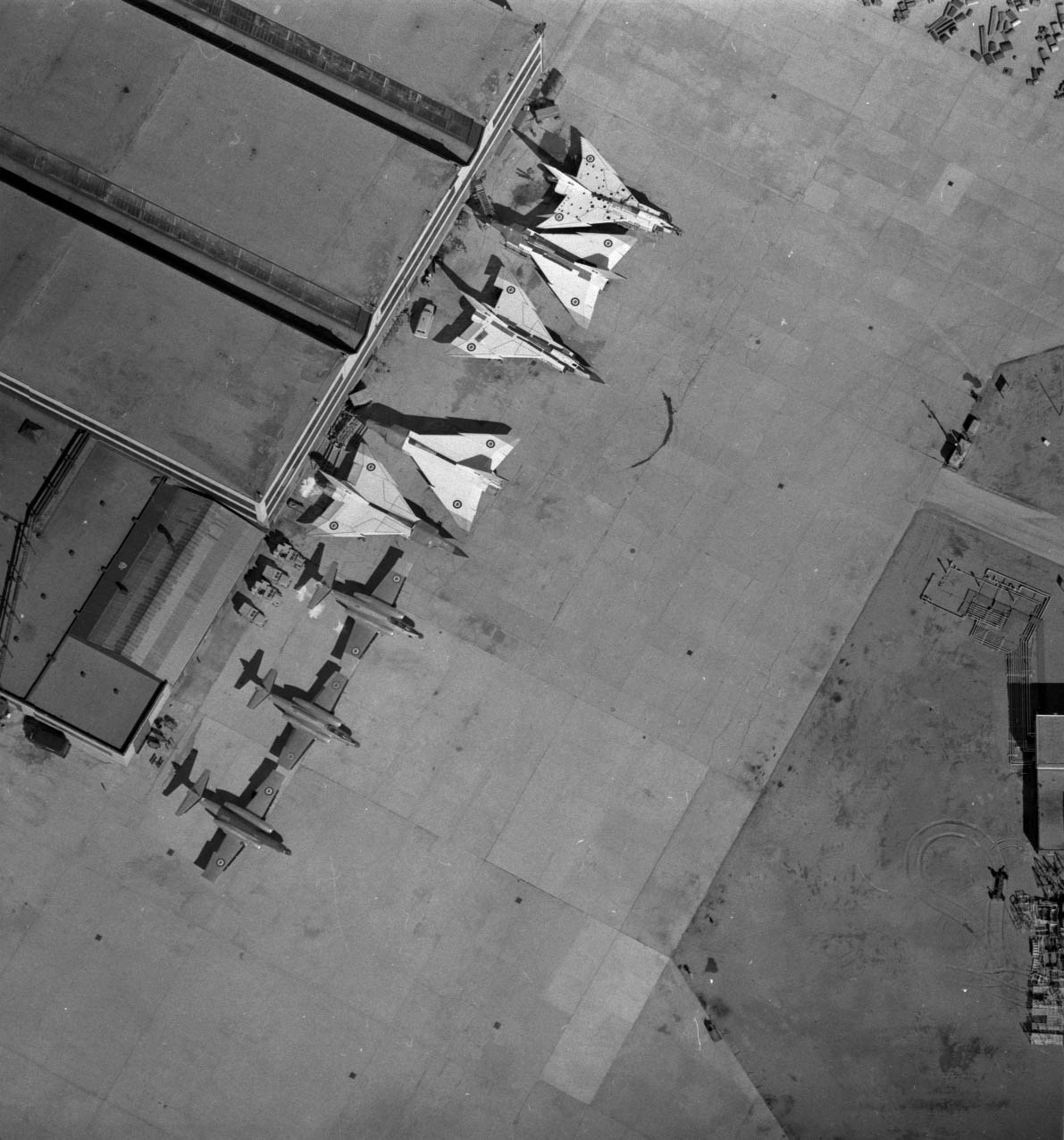 A black-and-white photograph of eight airplanes and a building, seen from above.