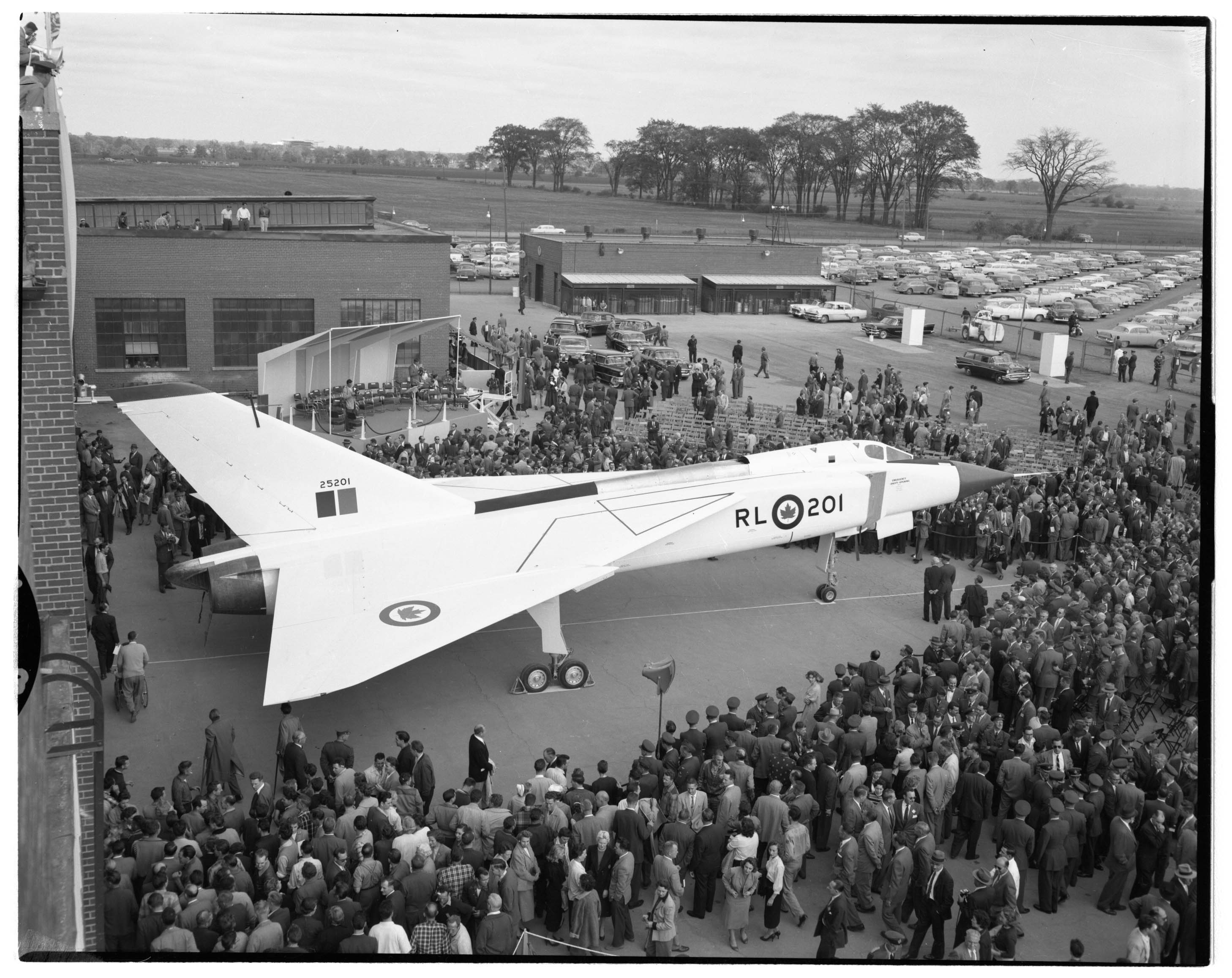 A black-and-white photograph of a crowd of people around a white aircraft.
