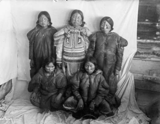 A black-and-white photograph of five Inuit women with facial tattoos standing in front of a white cloth backdrop