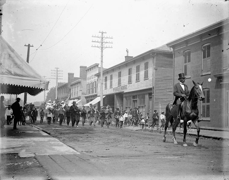 A crowd of people walk down the centre of the road in a small town parade. On either side, wooden storefronts line the street. The crowd, led by a distinguished mustached Black man wearing a top hat and tails and riding a horse, consists of a marching band, groups of small boys, and a handful of adults. Most of the people whose faces are visible in the crowd appear to be Black. In the background, a second horse pulls a parade float with women in white dresses and large hats.