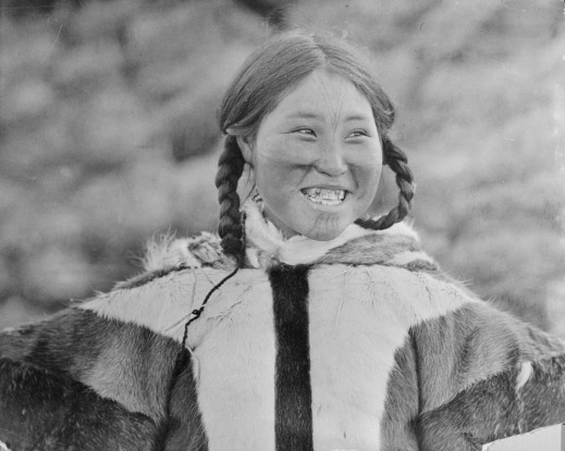 A black-and-white photograph of a smiling Inuk woman with facial tattoos.