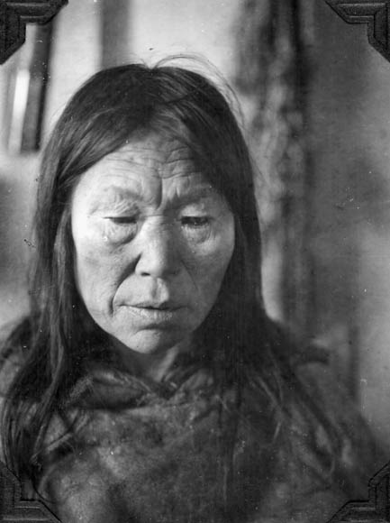 A black-and-white photograph of an Inuk woman in a fur parka.
