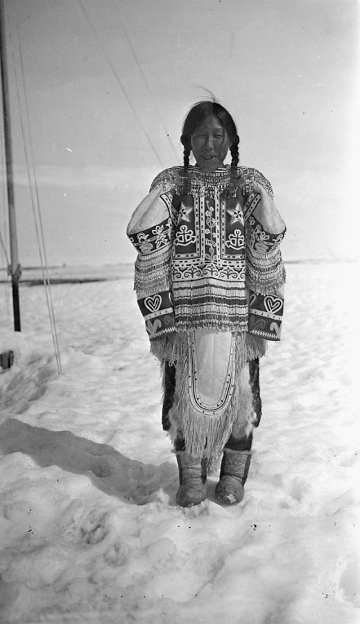 A black-and-white photo of an Inuk woman wearing a decorated parka standing in snow.