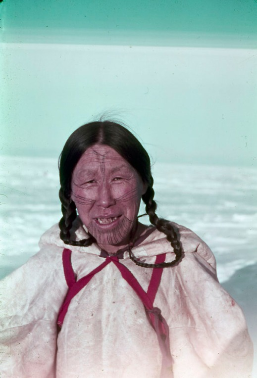 Left: A colour photo of an Inuk woman with facial tattoos wearing a white parka with red straps looking at the camera.