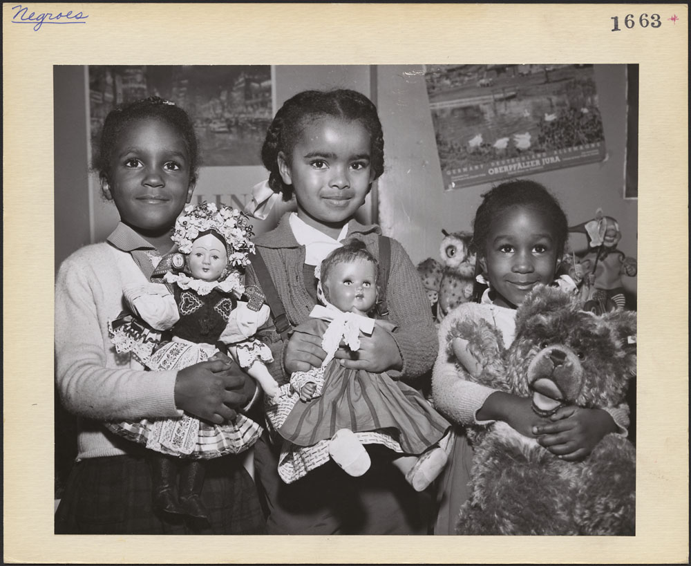 A black-and-white photograph of three little girls holding toys. The two girls on the left are holding porcelain dolls and the girl on the right is holding a large stuffed teddy bear. All three of the children, who are Black, are smiling shyly at the photographer and onlookers. They are dressed up, with their hair in braids and ribbons, and are standing in front of a poster-covered wall.