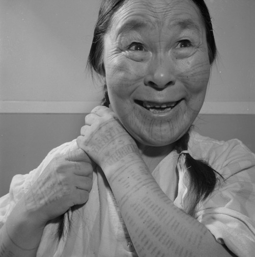 A black-and-white photograph of an Inuk woman with tattoos on her face and arms smiling while braiding her hair.