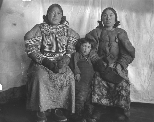 Black-and-white photograph of two women and a child wearing parkas, sitting in front of a fabric background.