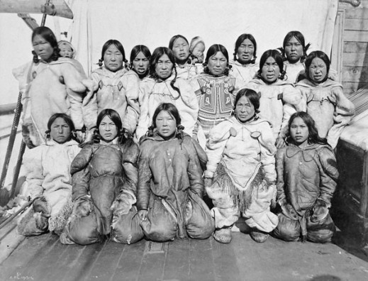 A black-and-white photo of 15 women and two babies, posed in three rows.