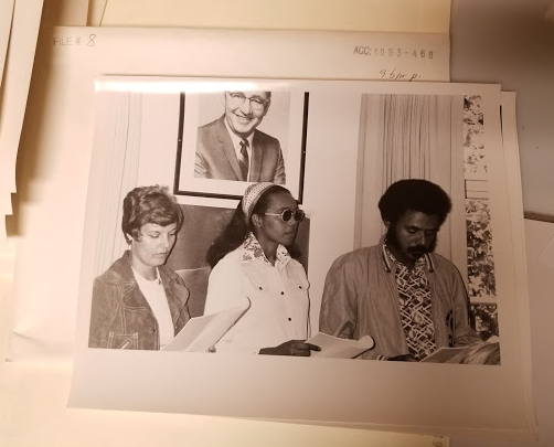Black and white photograph showing three young people seated at a meeting room table, holding what appear to be speaking notes or meeting agendas. On the left is a white woman with short cropped hair and a suede jacket. In the centre, a Black woman wearing sunglasses and wide headband. To the right, a Black man wearing a patterned shirt and plain coloured jacket. Behind them, on the wall above their heads, is a large formal photographic portrait of an older white man in a jacket and tie.