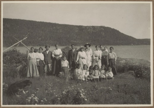 A black-and-white photograph of a group of men, women and children standing or sitting side by side in a field with flowers. There is water and land behind them, and a dog in the left foreground.