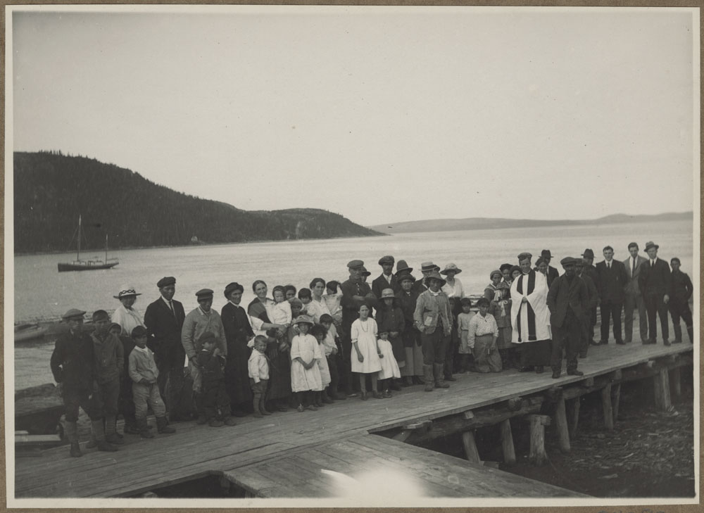 A black-and-white photograph of a large group of men, women and children standing on a pier with water behind them and a boat and land in the distance.