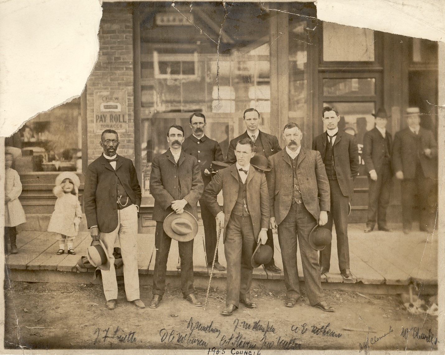 Black-and-white photograph of seven men in suits posing on a wooden sidewalk in front of a building entrance. Bystanders, including two men in suits and two unidentified young girls in white dresses and hats, appear in the background.