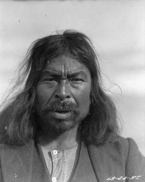 A black-and-white photo of a man with long hair and a mustache.