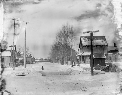 A black-and-white photograph of a street in winter. There is a signpost showing a railway crossing, houses, a person walking in the street and power line poles.