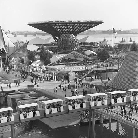 A black-and-white photograph of a crowd of people walking around large pavilions near the waterfront. There is a train with white cars in the foreground.