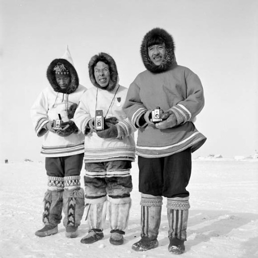 Black-and-white photo of three Inuit men standing outside in the winter. All three are dressed in traditional clothing.