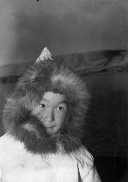 Black-and-white photo of a young boy wearing a fur-lined hood.