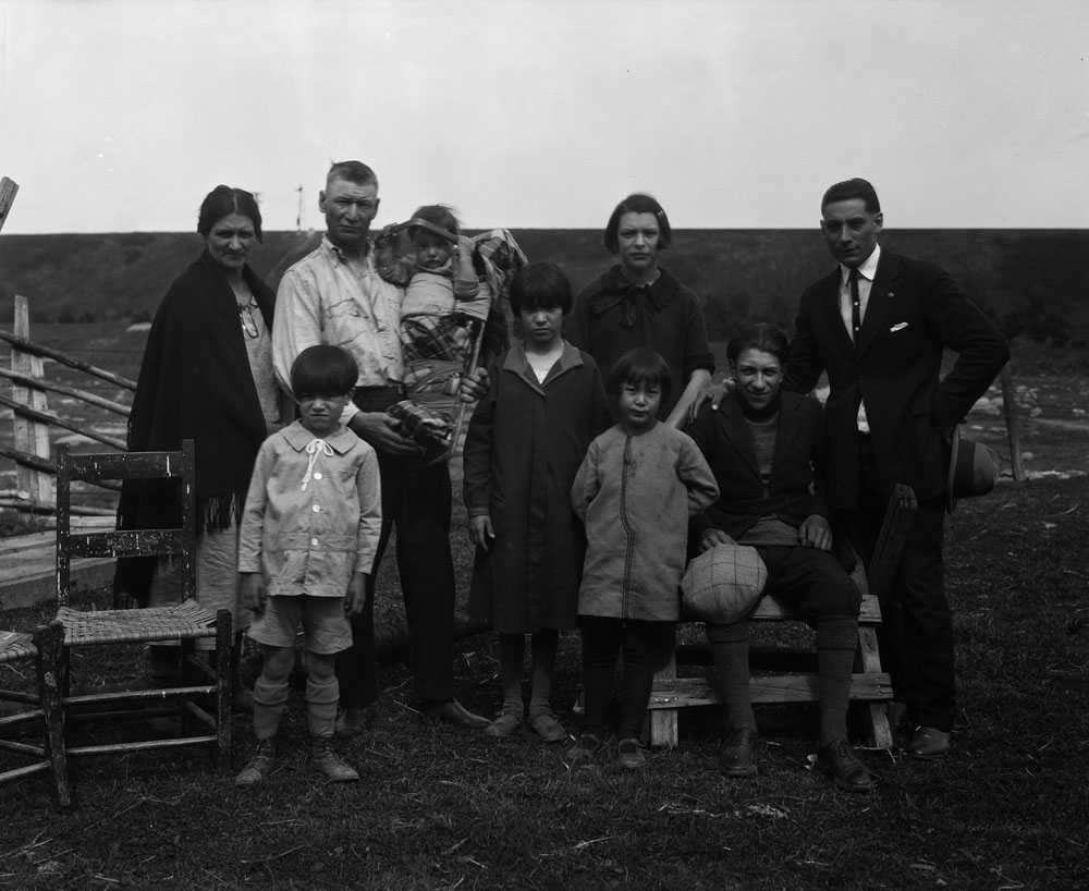 A black-and-white photograph of nine people facing the camera. A man is holding a baby in a cradleboard. Uncut brush landscape is in the background. There are no buildings on the horizon