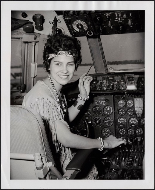 A black-and-white photograph of a woman smiling at the camera wearing buckskin regalia, a necklace, bracelets and a headband.