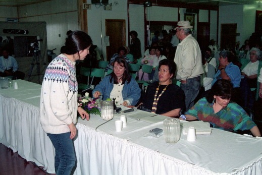 A colour photograph of a woman with a white sweater standing and talking to three women, who are seated on the other side of a long table.