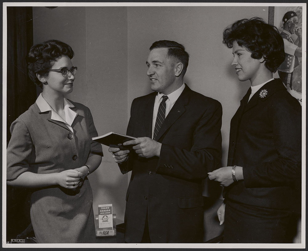 A black-and-white photograph of two women and a man in business attire.