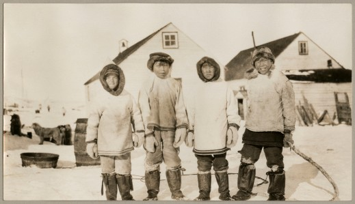 A black and white photograph of four boys in parkas looking towards the camera. There are two buildings in the background.