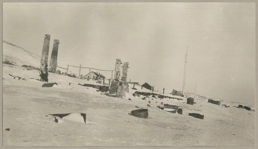 A black and white photograph of the ruins of a building with snow-covered items scattered around.