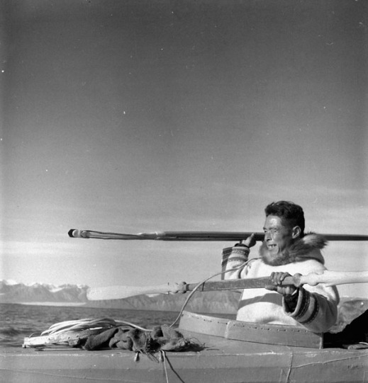 A black-and-white photograph showing a man in a qajaq about to throw a harpoon. There are snow-covered mountains in the distance.