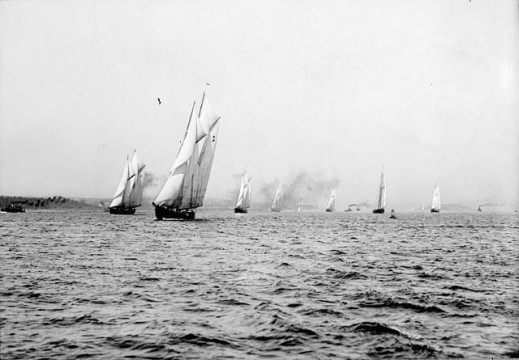 Black-and-white photograph of sailing vessels at the start of a race.