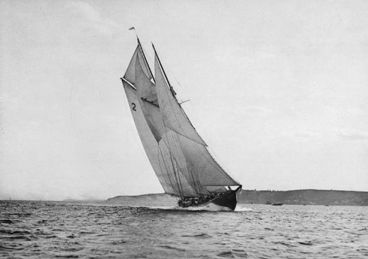 Black-and-white photograph of the Bluenose at the finishing line of a race.