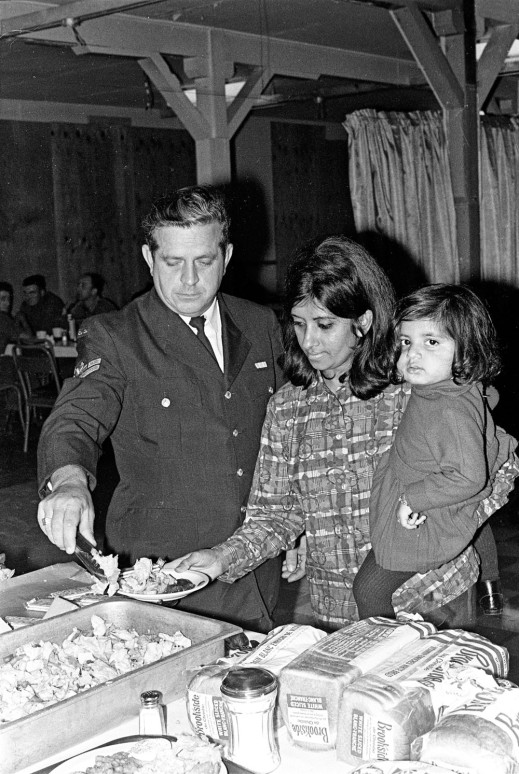 A black-and-white photograph of a man in a uniform serving food to a woman holding a small child.