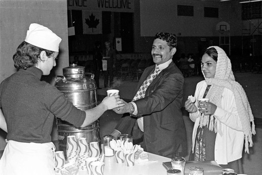 A black-and-white photograph of a woman in an apron and a hat handing a paper cup to a smiling man in a suit, as a woman in a scarf holds a cookie and a paper cup.