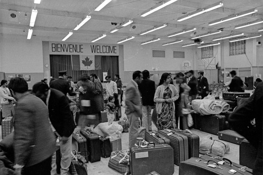 """A black-and-white photograph of a large group of people standing in a big room, with luggage and suitcases on the floor, and a Canadian flag and a sign reading """"Bienvenue, Welcome."""""""