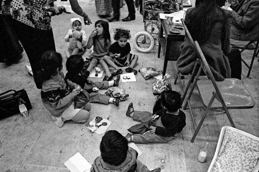 A black-and-white photograph of a group of children sitting together on the floor eating.