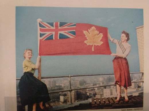 A colour photograph of two women holding a flag on a rooftop.