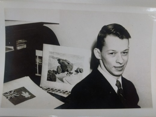 A black-and-white photograph of a man looking towards the camera with a flag design in the background.