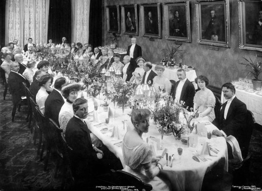 Black-and-white photo of people in formal attire seated around a long oval table. The table features place settings and decorative centrepieces.
