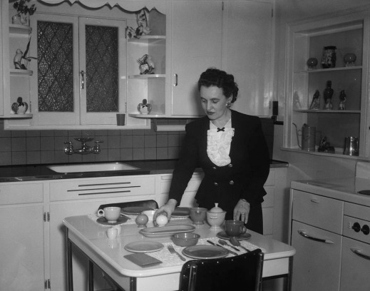Black-and-white photo of a woman setting the kitchen table.