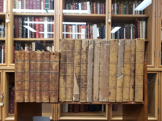 A colour photograph of aged hardcover books on a book truck, in front of a glass book cabinet.