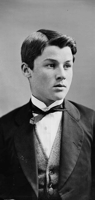 A black-and-white photograph of a boy in a suit.