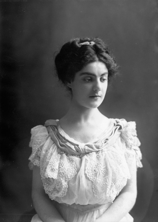 Black-and-white photo of a young woman in a white lace dress, facing the camera.