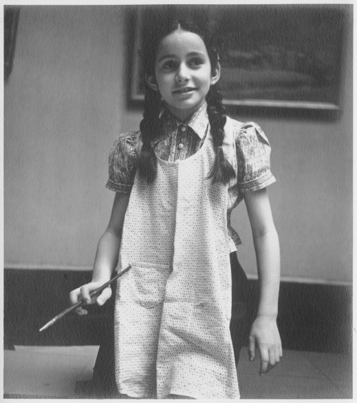 A black-and-white photograph of a girl with dark braids and a light apron kneeling on the floor and holding a paintbrush in her right hand. The bottom of a framed painting can be seen behind her.