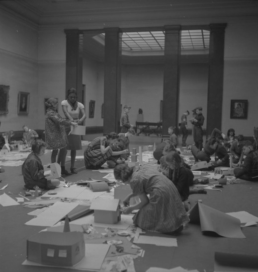 A black-and-white photograph of children kneeling in the middle of the floor in a gallery, surrounded by paper and art supplies. A teacher stands near the middle of the room, assisting a student. The walls are hung with framed paintings, and an adjacent gallery is visible behind four dark columns. The scene is full of energy as the children build paper houses.