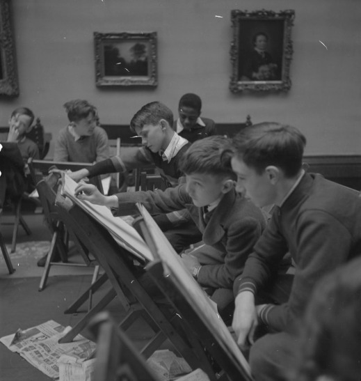A black-and-white photograph of six boys sitting on chairs in a gallery. Each boy has a second chair in front of him being used as a drawing easel. Two framed paintings can be seen on the wall in the background, and there are newspapers scattered on the floor.