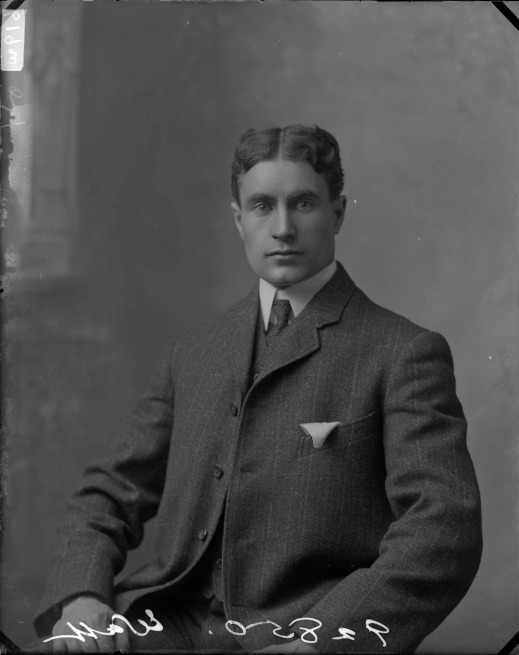 Black-and-white photo of a man in a dark suit, facing the camera.