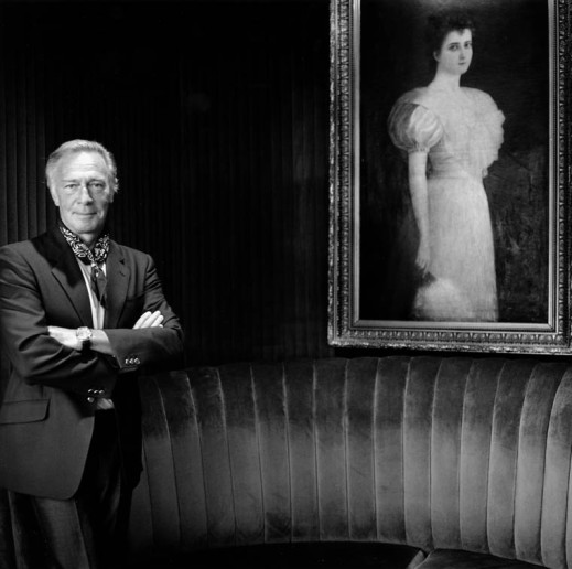 A black-and-white photograph of Christopher Plummer in a suit standing on the left with his arms crossed. A large framed painting of a woman in a dress holding a fan is hung on the right side.